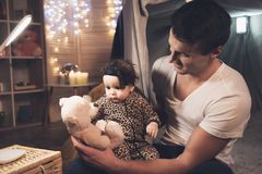 父亲在家使用与小小女儿在晚上 免版税库存照片