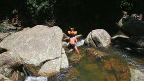 父亲在山河举行沿石头的小女孩攀登 影视素材