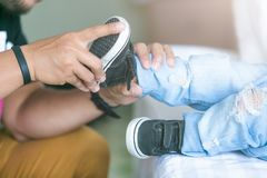 父亲在床上的屋子里帮助他的儿子栓他的鞋子 库存照片