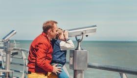 父亲在海双筒望远镜帮助他的小儿子看 免版税图库摄影
