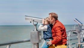 父亲在海双筒望远镜帮助他的小儿子看 免版税库存图片