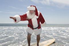 父亲在水的边缘的圣诞节冲浪板 免版税库存图片