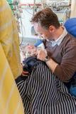 父亲坐在拿着他病的婴儿男孩的加护病房的一把椅子被包裹在医疗equipm围拢的毯子 免版税库存照片
