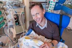 父亲坐在拿着他病的婴儿男孩的加护病房的一把椅子被包裹在医疗equipm围拢的毯子 库存图片