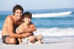 父亲坐的儿子游泳衣受麻烦 图库摄影