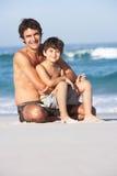 父亲坐的儿子游泳衣受麻烦 免版税图库摄影
