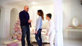父亲培养儿子,并且妇女母亲为孩子在明亮的卧室圣诞树和礼物调解自白天 股票视频