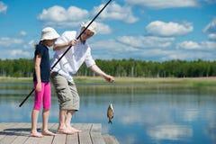 父亲女儿在河抓了一条鱼 免版税库存照片