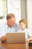 父亲家庭膝上型计算机儿子使用 免版税库存照片