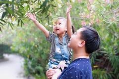 父亲容忍拥抱他的女儿微笑获得乐趣享受业余时间在与树的夏天公园愉快的儿童童年戏剧 免版税库存图片
