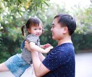 父亲容忍拥抱他的女儿微笑获得乐趣享受业余时间在与树的夏天公园愉快的儿童童年戏剧 库存图片