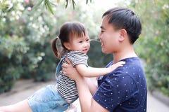 父亲容忍拥抱他的女儿微笑获得乐趣享受业余时间在与树的夏天公园愉快的儿童童年戏剧 免版税库存照片