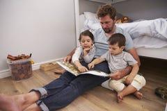 父亲对孩子的读书故事在他们的卧室 库存照片