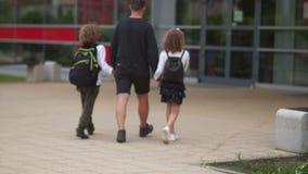 父亲带领他的孩子学校 一个人由胳膊拿着一个男孩和一个女孩 他们上有背包的学 回到 股票视频