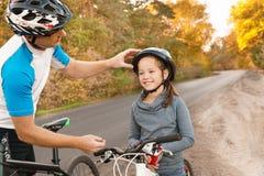 父亲帮助他的儿子乘驾自行车 免版税库存图片