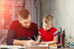 父亲帮助他的儿子做学校的家庭作业 图库摄影