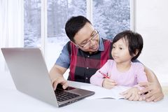 父亲帮助他的女儿用途膝上型计算机 库存照片