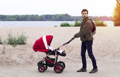 年轻父亲帮助母亲,他走与在的一辆婴儿车 免版税库存照片