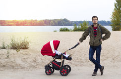 年轻父亲帮助母亲,他走与在的一辆婴儿车 库存照片