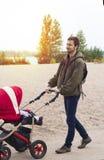 年轻父亲帮助母亲,他走与在的一辆婴儿车 免版税库存图片