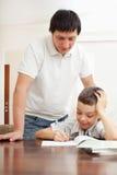 父亲帮助的儿子做家庭作业 库存图片