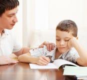 父亲帮助的孩子做家庭作业 库存照片