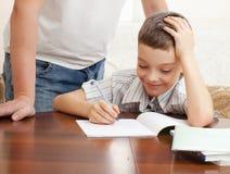 父亲帮助的男孩做家庭作业 免版税图库摄影