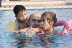 父亲开玩笑池游泳 库存图片