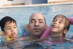 父亲开玩笑池游泳 库存照片