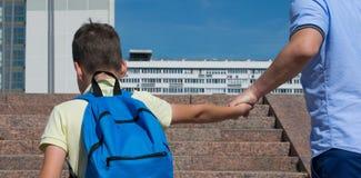 父亲强有力地把他的儿子带到学校,台阶 免版税库存照片