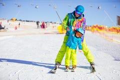 父亲或辅导员教小滑雪者如何做轮 免版税库存图片