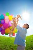 父亲投掷女儿。一起使用在有ba的公园的法米利 库存照片