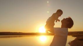 父亲抱着红色晚上太阳的胳膊的小婴孩 慢的行动 股票录像
