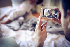 父亲拍他的妻子照片,并且女儿有使用 免版税库存照片