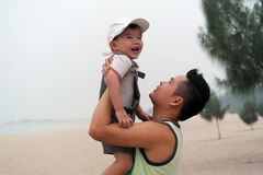 父亲拥抱海滩的儿子 免版税图库摄影