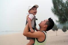 父亲拥抱海滩的儿子 库存照片