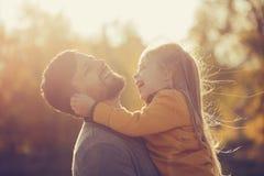 父亲拿着他的胳膊的女儿 免版税库存图片