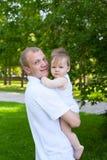 父亲拿着男婴的爸爸父母 免版税库存图片