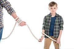 父亲拿着绳索的播种的射击和被栓的小儿子 库存图片