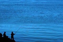 父亲捕鱼剪影儿子 免版税库存照片
