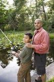父亲捕鱼西班牙池塘儿子 免版税库存照片