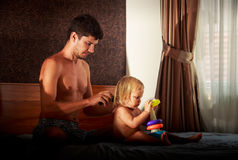 父亲掠过他的小白肤金发的女儿的头发 免版税库存图片