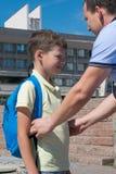 父亲改正他的儿子学校背包 免版税图库摄影