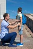 父亲改正他的儿子,一条蓝色学校背包皮带 免版税库存照片