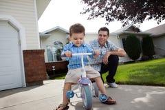 父亲教对三轮车的乘驾儿子 免版税图库摄影
