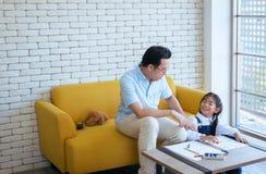 父亲教少女孩子一起做家庭作业,愉快和乐趣,家庭爱 免版税库存图片