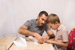 父亲教他的儿子做纸飞机 免版税库存图片