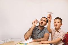 父亲教他的儿子做纸飞机 免版税图库摄影