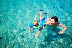 父亲教他的小儿子在海游泳 免版税库存照片