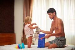父亲显示新的礼服给小女儿由明亮的窗口 库存图片